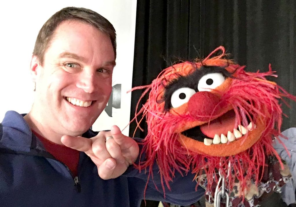 A photo of Chris Sebes with the Muppet known as Animal.